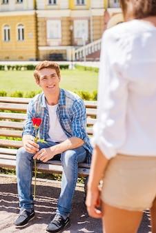 Наконец-то встречаемся! счастливый молодой человек сидит на скамейке и держит одну розу с женщиной на переднем плане