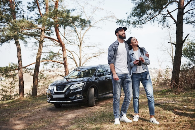 Finally sunny day. embracing and enjoying the nature. couple have arrived to the forest on their brand new black car