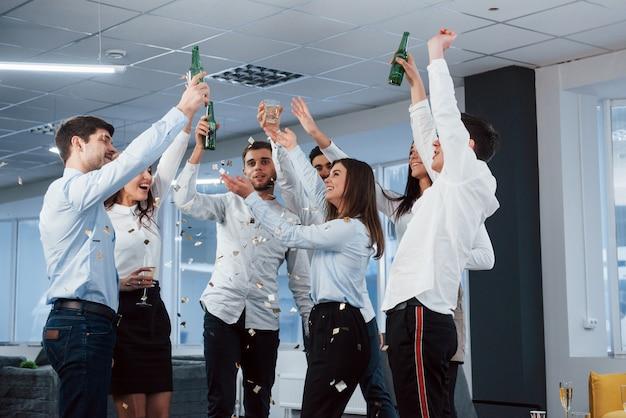 最後にそれを得た。モダンな照明付きのオフィスで飲み物を押しながら成功を祝うクラシックな服装の若いチームの写真