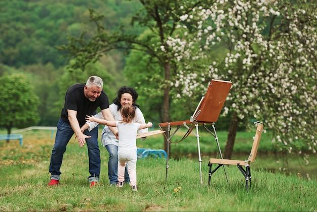 最後に会った。祖母と祖父は孫娘と屋外で楽しんでいます。絵画の構想
