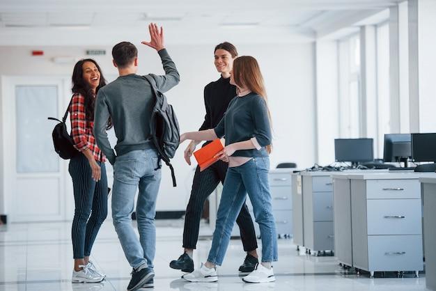 드디어 만났습니다. 휴식 시간에 사무실에서 걷는 젊은 사람들의 그룹입니다.