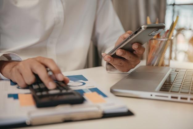 Концепция финансового учета. бизнесмен, работающий со смартфоном и использующий калькулятор для расчета количества статического электричества в офисе.
