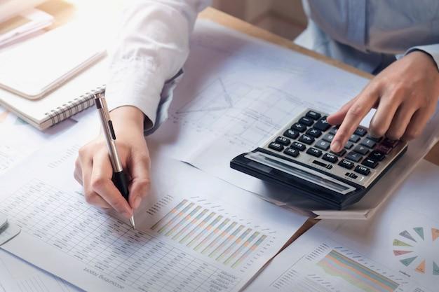Концепция финансов и бухгалтерского учета. деловая женщина работает на столе с помощью калькулятора