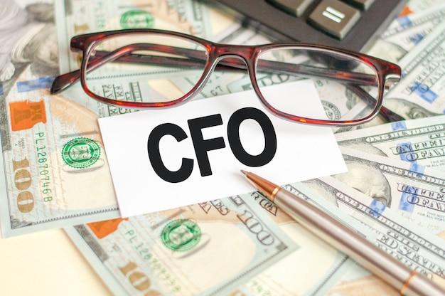 金融とビジネスの概念。テーブルの上には、請求書、眼鏡、ペン、そしてそれが書かれている看板があります-cfo。 cfo-最高財務責任者
