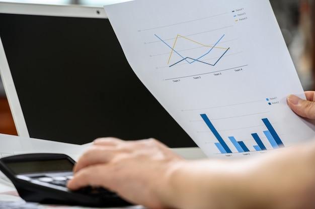 金融とビジネスのコンセプトです。財務グラフを保持している実業家の手。