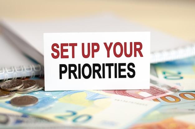 Концепция финансов и экономики. на столе банкноты, пачка долларов и табличка, на которой написано - расставьте приоритеты.