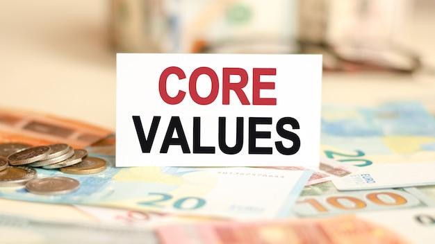 Концепция финансов и экономики. на столе купюры, монеты и знак, на котором написано - основные ценности.