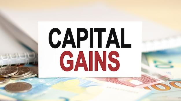 テーブルの上の金融と経済の概念は、それがキャピタルゲインと書かれている紙幣コインとホワイトペーパーサインです