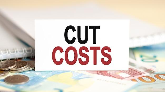 금융 및 경제 개념. 테이블에는 지폐, 동전 및 백서 사인이 적혀 있습니다-비용 절감