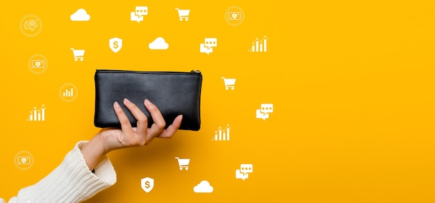 Finance asian woman with a black wallet full of money ready to go shopping finance is streamlined, successful in finance and banking. on a yellow background
