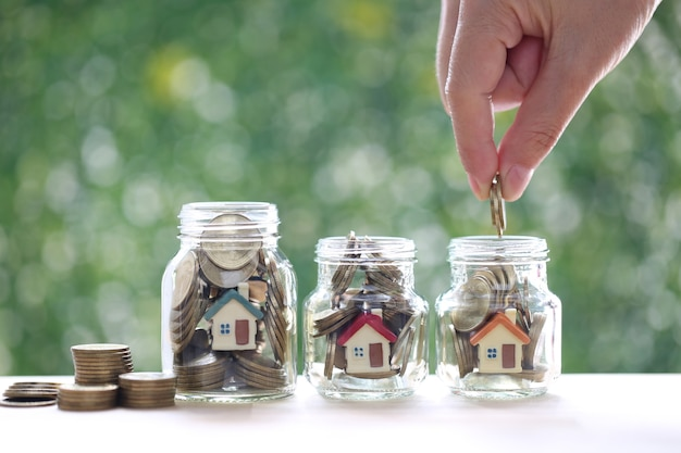 Finance and banking, model house and gold coin money in the glass bottle on green background,business investment and real estate concept
