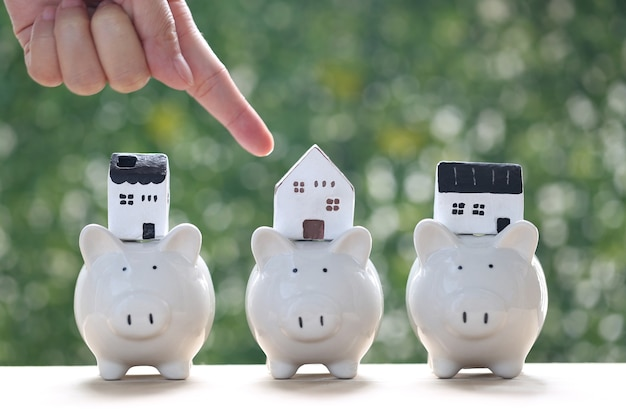 Finance and banking, model house on piggy bank with stack of coins money on nature green background,business investment and real estate concept