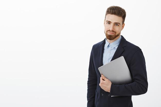 金融、ビジネス、テクノロジーのコンセプト。自信に満ちた表情でニヤリと腕を組んでラップトップコンピューターを保持しているスタイリッシュなスーツでひげと青い目を持つ魅力的なエレガントな若い男