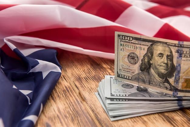 アメリカの金融の旗の上に横たわる金融コンセプトドル紙幣