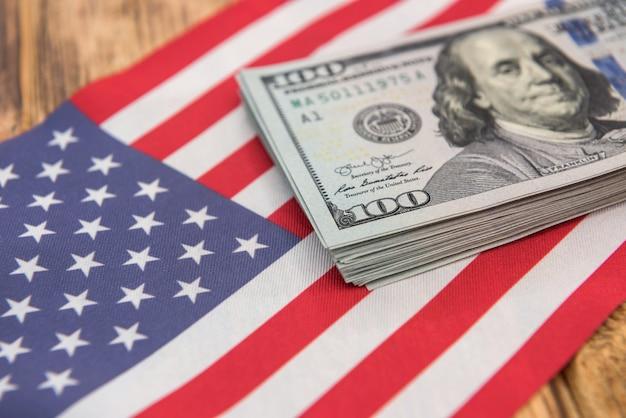 アメリカの国旗に横たわっている金融コンセプトのドル紙幣。ファイナンス