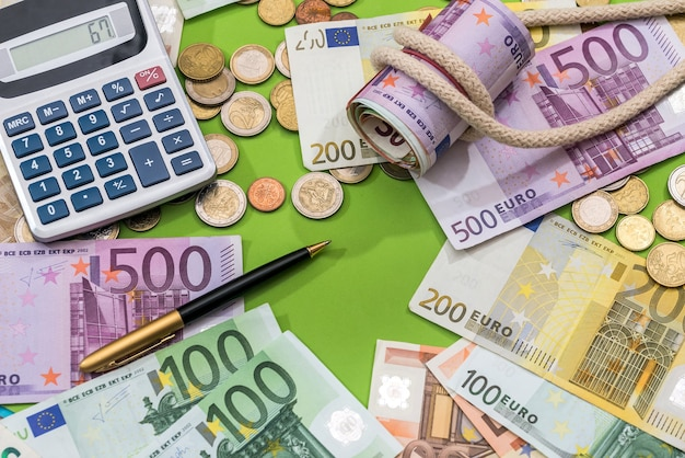 Finance concept euro banknote and coin with calculator and pen