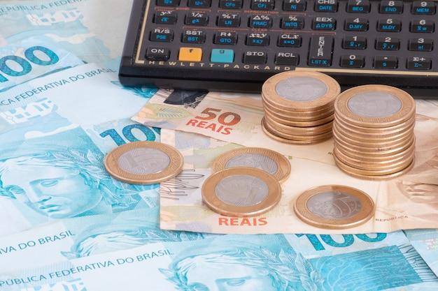 ファイナンスのコンセプト電卓とペンブラジルのお金で100レアル紙幣と硬貨