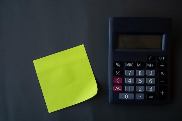 Финансовая концепция, напоминание и калькулятор на черном фоне