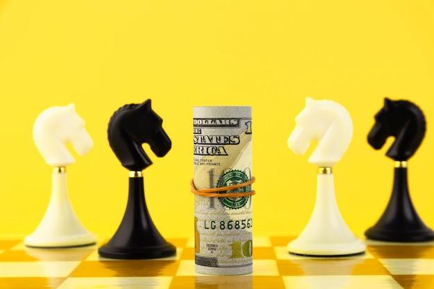 Концепция финансов с долларовыми купюрами и шахматной лошадью