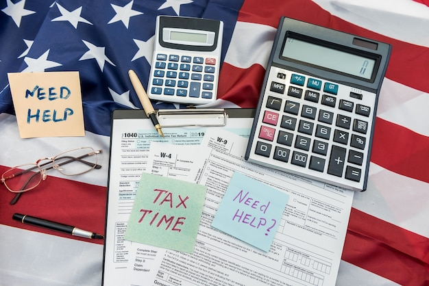 Finance document 1040 tax form with pen and calculator on flag of usa. deadline