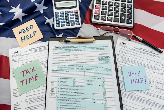 Finance document 1040 tax form with pen and calculator on flag of usa
