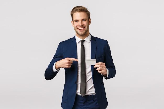 金融、起業家、ビジネスコンセプト。ハンサムな陽気な青年実業家は、新しい銀行についてパートナーに相談し、クレジットカードを保持して、それを指して、白い背景をお勧めします
