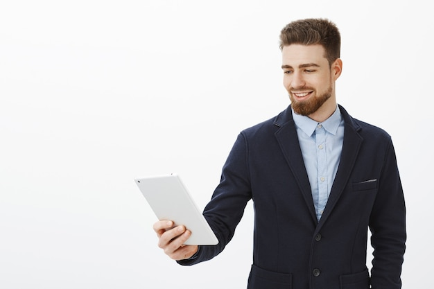 金融、ギグ経済、ビジネスコンセプト。自信に満ちた笑顔で満足するガジェット画面を見つめるデジタルタブレットを保持しているエレガントでスタイリッシュなスーツを着た自信を持って喜んで成功した男性起業家
