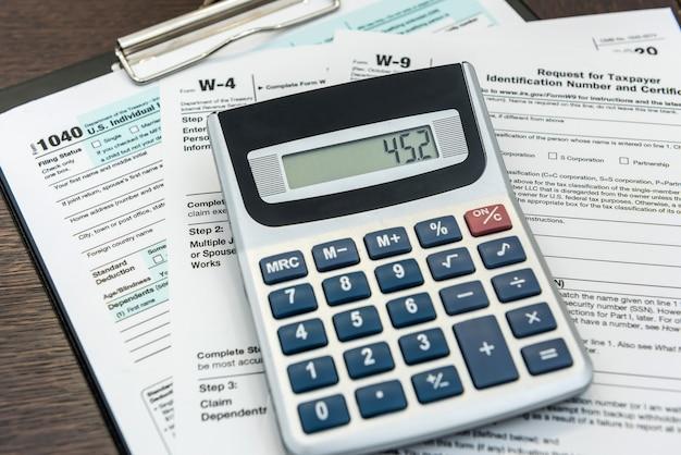 財政収入、税計算機、および連邦政府のフォームに横たわっているペン。締め切り