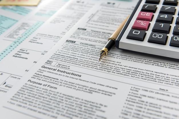 財政収入、税計算機の時間、および連邦政府のフォームに横たわっているペン。締め切り