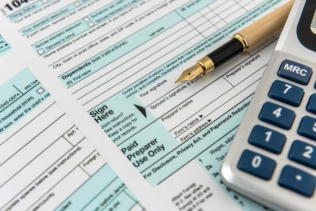 金融収入、納税額計算機、連邦用紙に横たわるペン