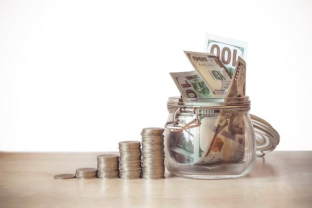 금융, 투자 및 퇴직 계획 개념입니다. 다른 높이의 동전 더미는 경제 성장을 상징하고, 지폐가 있는 유리 은행, 특정 목적을 위해 저축하는 상징입니다.