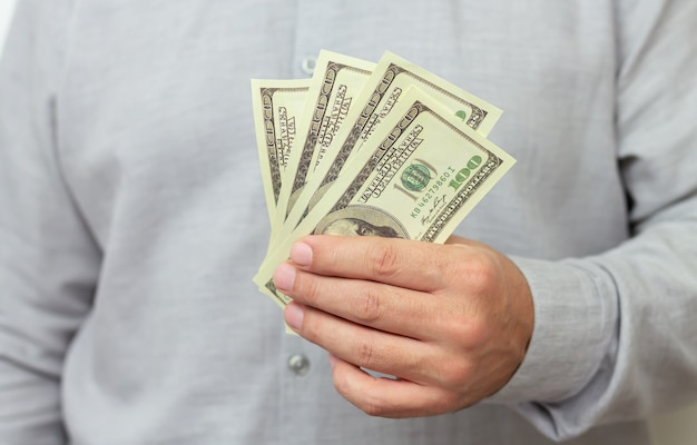 Finance, investment or money saving concept. man holding paper us dollars