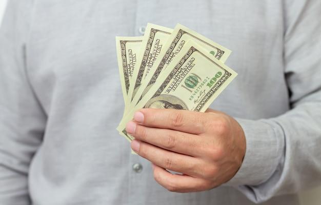 金融、投資またはお金の節約の概念。紙を持っている男私たちドル