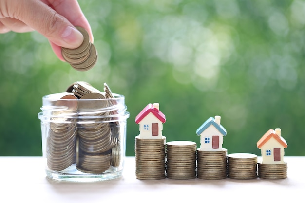 Finance, model house on stack of coins money on natural green background, business investment and real estate
