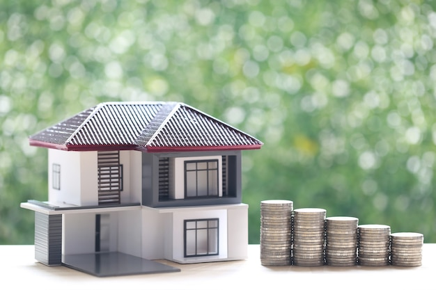 Finance, model house with stack of coins money on natural green background, saving money for prepare in future and investment concept