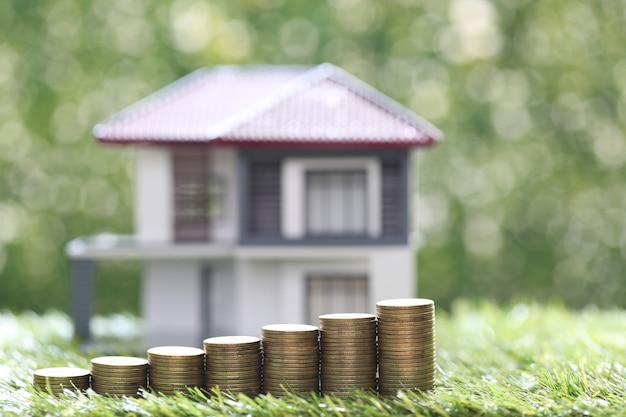 Финансы, модельный дом со стопкой монет денег на естественном зеленом фоне, экономия денег для подготовки в будущем и инвестиционной концепции