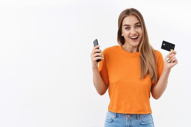 金融、お金、銀行の概念。幸せな、ブロンドの女の子の肖像画は彼女の給料を手に入れました、新しい服をオンラインショッピングで購入し、携帯電話とクレジットカードを持って、広く笑っています