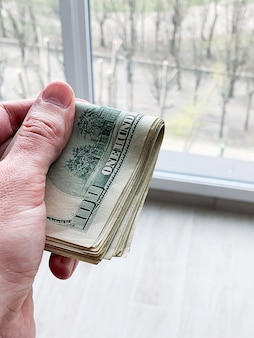 Finance money. man holding a hundred dollars banknotes for rental or purchase flat