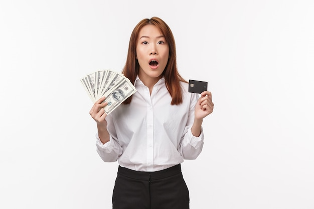 Finance, money and shopping concept. excited and shocked young asian woman holding dollars and credit card, look at camera nervously, want waste money on vacation, making decision,