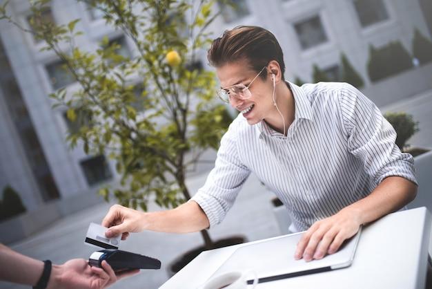 Финансовая оплата наличными бесплатно и люди концепции молодой человек с кредитной картой, оплачивающей кофе в городе s