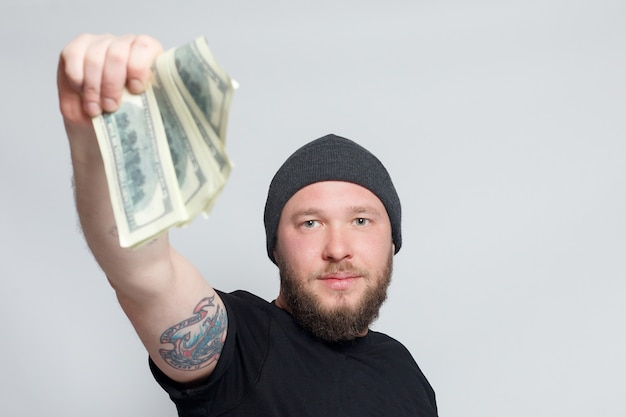 금융, 사람, 라이프 스타일 개념-수염 난된 남자. 재밌는 녀석은 행운의 승자이고, 그녀는 돈 더미를 들고 있고, 그는 놀랐고 그것을 믿을 수 없으며, 그는 백만 달러 잭팟을 이겨서 기쁩니다