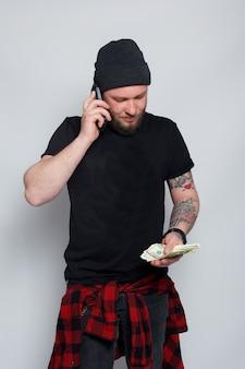 金融、人、ライフスタイルのコンセプト-あごひげを生やした男。面白い男は幸運な勝者です、彼女はお金の山を持っています、彼は驚いてそれを信じることができません、彼は100万ドルのジャックポットを勝ち取って幸せです