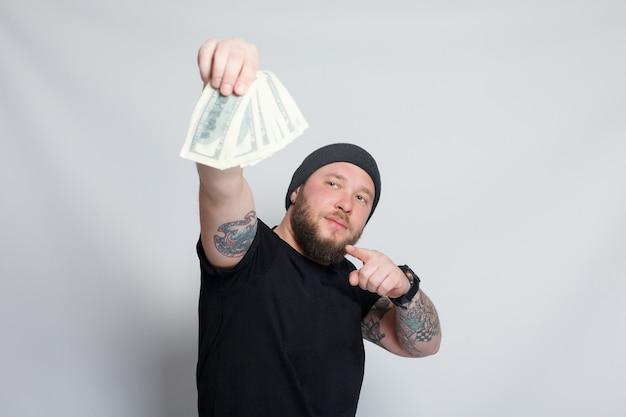 금융, 사람, 라이프 스타일 개념 - 수염 난 남자. 재미있는 사람은 운이 좋은 승자이고, 그녀는 돈 더미를 들고 있고, 그는 놀라고 믿을 수 없습니다. 그는 백만 달러 잭팟에 당첨되어 기쁩니다 프리미엄 사진