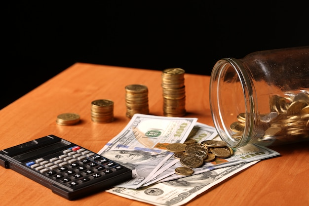 A finance still life with a jar of sterling coins on sterling notes, calculator dollars on the table