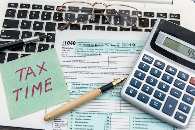 Finance tax form with calculator, laptop and pen