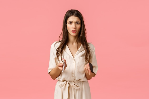 Finance, technology concept. troubled and worried young frustrated woman cant understand what happened, frowning looking perplexed and cocnerned, holding credit card with phone, pink wall