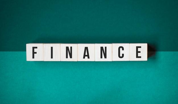 木製の立方体の財政の言葉。投資と貯蓄の概念。オレンジ色の背景に分離された文字と木製のブロック。