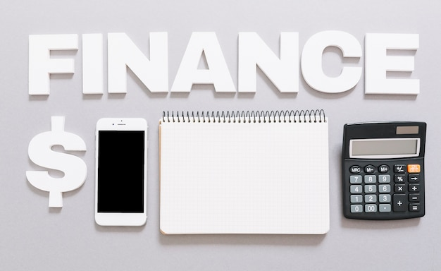 Finance word with dollar sign; cellphone; spiral notebook and calculator on gray background