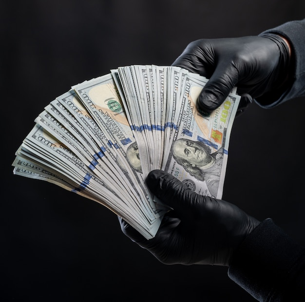 財政の概念。黒の背景の上にドルのパックを保持している黒い手袋の男