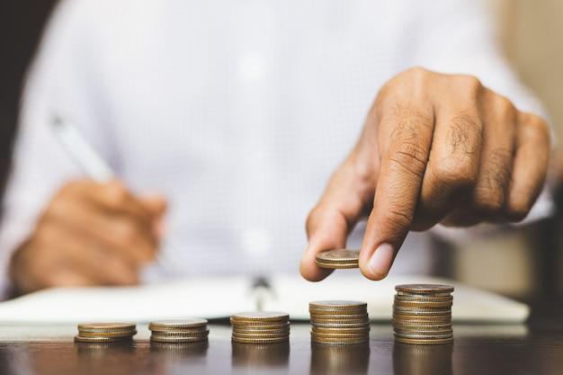 Концепция банковского сбережения финансов. деловой человек укладки монет.